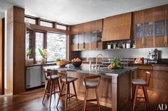 This Aspen, Colorado, kitchen is outfitted with oak cabinetry and circa-1960 H. Rosengren Hansen barstools from Wyeth; the floor is reclaimed oak. The home was designed by Studio Sofield in collaboration with Studio B Architects.