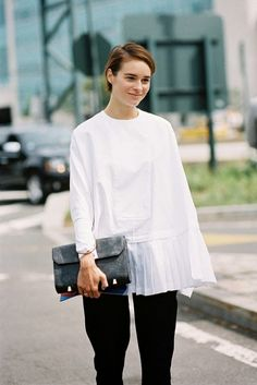 A white oversized pleated top is worn with black bottoms and accessorized with a black clutch.