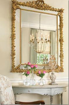 The dining room chandelier is reflected in the mirror above an antique Swedish demi lune.