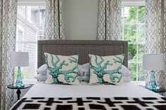 Modern Nautical Bedroom in Nantucket. Love the mix of the bold graphic black & white curtains and throw blanket with the traditional upholstered headboard accented by nail head trim. Fun coral print accent pillows and serene aqua blue glass table lamps. Soothing gray walls. From Rachel Reider Interior Designs.