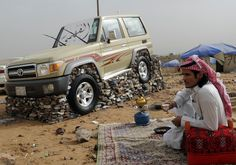 Friday july 13, 2012. Young Saudi is showing off with his car at a get together. The car is placed on a stand of loose rocks.