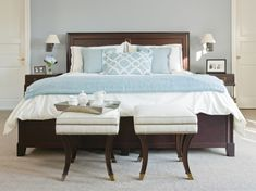 The master bedroom is the picture of serenity | dark brown wood bed frame | nailhead trim upholstered stools | end of the bed ottomans | blue and ivory | neutral bedroom