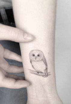 Small owl tattoo on wrist by Jakub Nowicz