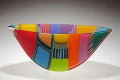 Ruth Shelley - Sisial Collection (Whisperings) {phonetic - Sishal} is based on a development of assembling glass in various length strips and arranging them on edge to form various shapes which gives great freedom in design, colour and form. It is then carefully fused, shaped and coldworked. The collection concentrate mainly on the Colours that adhere Wales together in a 'Wales Adhesion' Range (Gludiad Cymru) {phonetic - Glydiad Kymry} They are vibrant, unique, and full of colour and…