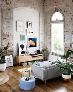 Nice Living Room Idea With Grey Sofa Brick Wall Indoor Plants And Abstract Art
