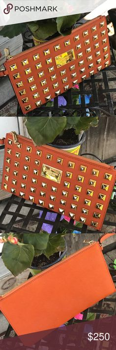 """🔥Gorgeous🔥 L/E Tangerine Gold Pyramid Studded 🔥 Limited Edition & very hard to find in beautiful , gently used condition 🔥HOT🔥 tangerine gold pyramid Studded large wristlet clutch ! Measure's 10""""(L)X6""""(H) , 8 cc slots & still lots of space ! Any Q's just tag me 😍! Thanks KORS Michael Kors Bags Clutches & Wristlets"""