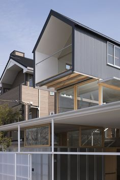 House in Ishikiri.  Dark concrete walls and a black archetypical house volume above it, a translucent lean-to roof, a white high flat roof and a silver box under it. Those totally different and inconsistent materials and colors are combined to form this house.