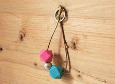 Schlüsselanhänger mit selbstbemalten geometrischen Holzperlen in rosa und helltürkis, runder Perle in champagnerfarben, aufgefädelt auf ein gold-braunes Wildlederband. Die selbstbemalten Perlen wurden mit Acrylfarbe bemalt und anschließend matt lackiert. Gerne kann ich diesen Schlüsselanhänger auch individuell nach deinen Wünschen zusammenstellen, z.B. mit anderen Perlen oder in einer anderen Länge.
