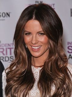 How to Get Kate Beckinsale's Flirty Voluminous Waves:  Starting with a center part, apply volumizing mousse to top half of hair  blow dry straight with a round brush, lifting hair at roots.  Curl bottom half of hair in 2 in. sections with a 1.5 in. curling iron, wrapping hair around the iron outward.  Rake fingers through waves  mist with glossing spray to finish.