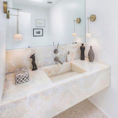 This sink made of onyx has a hidden channel drain that doesnt draw attention away from the rich detail of the rock. #MidCentury #Architecture #ModernArchitecture #ContemporaryArchitecture #BelAir #LosAngeles #California #InteriorDecorating #InteriorDesignIdeas #DesignIdeas #HomeDesign #LuxuryRealEstate #LuxuryListings #LuxuriousListings #ModernDesign #ContemporaryDesign #InteriorDesign #Design #MasterBathroom #BathroomIdeas #OnyxSink #OnyxCounterTop #ModernBathroom #LuxuryBathroom…