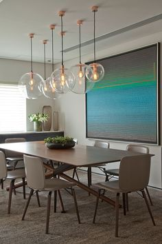 Decoração de apartamento duplex com alta tecnologia, nos detalhes da decoração da sala de jantar pendentes, mesa de madeira, plantas na decoração.