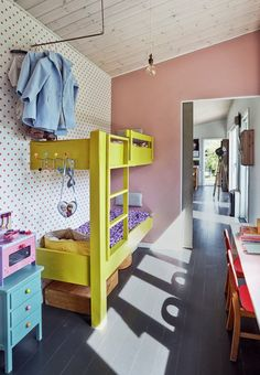 Colorful girls room with pink wall color and yellow bunk beds.