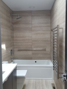 Large striated tiles, heated towel bar, recessed shampoo niche, Kohler faucets, toilet and tub