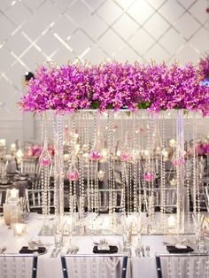 Gorgeous crystal garland centerpieces with purple flowers for a sparkling wedding table design.