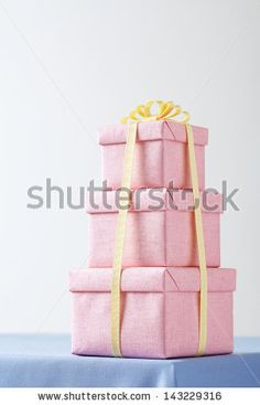 Table covered with a blue cloth with pink gift box. pink gift boxs.
