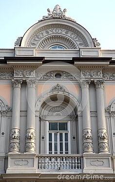 Photo taken with an elegant and historic palace in Trieste in Friuli Venezia Giulia (Italy). The picture shows a detail of the facade. The balcony is framed between two elegant columns on each side, columns holding up a semi-circular structure that rises above the frame of the roof and at the top you see two small statues on either side of a coat of arms.