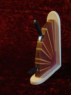 This is a Hardwood Knife block with dramatic radiating white oak and Jatoba rays from a Purple Heart sun, all mounted on Maple. The graduated, tapered slots hold four usual graduated kitchen knives from small to large. The two knives shown are not included. Slots: from the top: 8, 9, 6 1/2, 6
