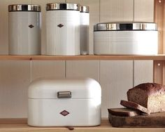 Williams-Sonoma offers a range of storage containers from venerable German company Wesco. A set of three Wesco Canisters (top shelf left) is $99.95; available in white or red. The Wesco Cookie Box (top shelf right) is $59.95; available in white or red. The Wesco Grandy Bread Box (bottom shelf) is available in white, gray, or red; $79.95.