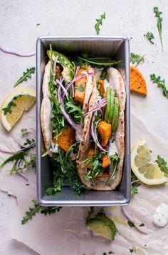 {Roasted sweet potato pitas with arugula and garlic dressing.}