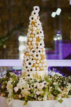 Incredible croquembouche wedding cake created by Couture Cakes sitting on a faux flower garland made by Friend of Faux