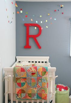 cute idea to place the crib in the corner with a single initial. the hanging decoration in place of a mobile.