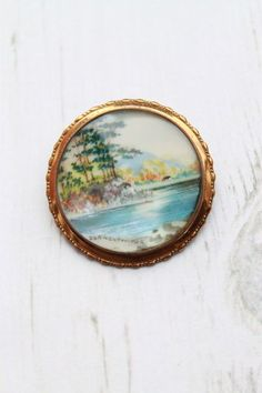 'TLM (Thomas L Mott) Singed Hand Painted River Round Brooch Pin' - Beautiful Art Deco TLM fully signed brooch circa 1930. Featuring a detailed river scene of Derwentwater one of the principal bodies of water in the Lake District National Park in north west England. The miniature painting is set into a brass frame with a domed glass front.