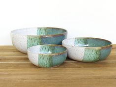 This set of three nesting pottery bowls is wheel thrown in a speckled brown stoneware clay and glazed in sea mist and white glazes. The overlap of the two glazes produces this amazing color and texture! The sea mist portion is a deep greeny-blue and the white portion is an opaque, glossy white with lots of speckles coming through from the clay.  The smallest bowl is 4 1/4 inches wide and 1 3/4 inches tall. The medium bowl is 6 inches wide and 2 inches tall. The large serving bowl is 7 7/8…