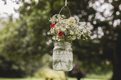 Pretty hanging jars with flowers for an outdoor wedding ceremony | www.onefabday.com