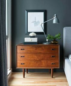 Gorgeous mid century night stand with art, task lamp and styling. Dark grey walls in bedroom.