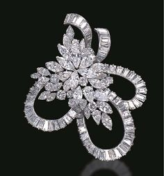 A DIAMOND SPRAY BROOCH The undulating baguette-cut diamond ribbon, gathered by a circular, pear and marquise-cut diamond floral spray, mounted in platinum