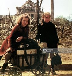 Two girls with a handcart are pausing amid the ruins of the city. July 1945. More than 300 bombardments by the British Royal Air Force (RAF) and the United States Army Air Forces took place in the period from June 1940 to the end of the war in 1945. Berlin, Germany.