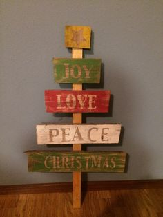 Christmas Tree made from an old pallet.   Letter stencils cut from the Cricut.