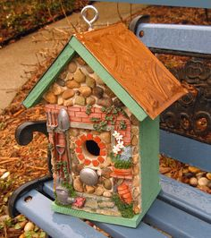 """$55    Welcome to My Garden Cedar birdhouses stained with 10 yr. deck stain in garden green. Roof is embossed faux copper. ( it was raining when I took this photo..hence the raindrops on the roof ) Only front is embellished with river rock, pebbles, silver tone knob for perch, multi-colored surround and miniature glazed tiles.  Removable base for easy clean out.  11 1/2"""" high X 8 1/2"""" wide X 6 1/4"""" deep      1 1/4"""" opening"""