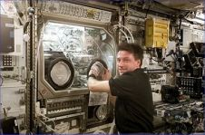 NASA astronaut Michael Foale performs an inspection of the Microgravity Science Glovebox (MSG) during Expedition 8 aboard the International Space Station. Image Credit: NASA