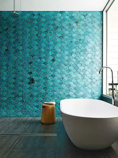 Baño con azulejos de escamas azules turquesa y bañera