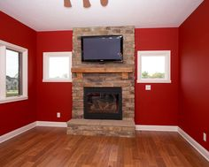 fireplace; red; stone fireplace; hardwood floors; television above fireplace