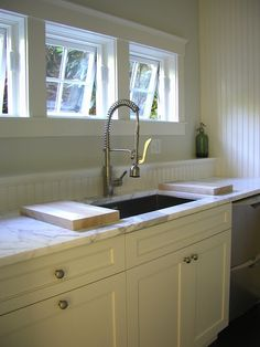 Kitchen with creamy white cabinetry with carrara marble countertops and beadboard backsplash.