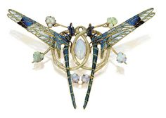A beautiful brooch/pendant by made by Lalique in 1903/1904 set with white opals in enamelled gold. The most striking feature are the two facing dragonflies which wings are applied with plique-a-jour enamel so delicate and transparent that it almost looks like coloured glass!.