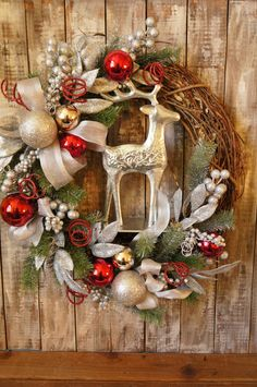 An embossed silver reindeer adorns a silvery Christmas wreath the perfect front door wreath for Christmas decorating. Celebrate the season with this large handmade reindeer Christmas wreath featuring sparkly silver ornaments and glittery pine boughs. A Beautiful Christmas decoration to hang in your home or on your door. Silver and red ornaments, glitter twists and silver ribbon are scattered amongst sparkled pine boughs. The embossed silver metal reindeer stands in the center of the…