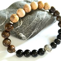 Just like a properly poured pint of stout!   Handmade - bronzite, picture jasper & onyx agate gemstones, silver-plated pewter Celtic knot accent. Comfort-stretch design  Gift for: •Guinness & beer lovers •Fans of all things Irish  Gift-ready packaging.