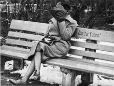 """Еврейская женщина, которая скрывает ее лицо сидит на скамейке в парке с надписью «Только для евреев"""". Австрия, 1938"""
