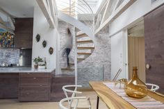 When Alan Ricks and Cristina de la Cierva moved into their Boston condo, a ship's ladder was taking up space in the main living area. Following a lengthy renovation, a spiral staircase provides rooftop access.