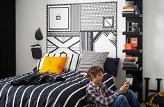 Slaapkamer met DIY-hoofdbord gemaakt van textieltape in zwart en wit; monochroom TUVBRÄCKA dekbedovertrek; oranje STOCKHOLM kussen