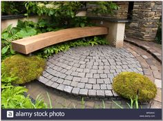 Patio of bluestone pavers with curving bench moss ferns stone pillars wall