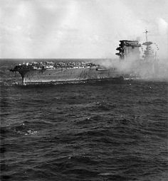 The crew of USS Lexington abandon ship. The destroyer alongside is taking off the sick and wounded while the able-bodied are sliding down ropes and being picked up by small boats...