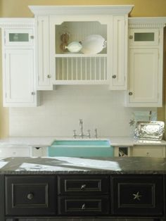 Designer Anissa Swanzy paired white cabinets with a green farmhouse sink for a clean, crisp look.