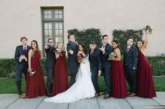 Long beach burgundy wedding at the ebell of long beach bride lace gown with thick straps and low back design with plunging neckline and bow on back with groom navy blue suit with matching vest and white dress shirt with long burgundy tie and matching pocket square with red floral boutonniere with bridesmaids long burgundy dresses and groomsmen navy blue suits with long burgundy ties