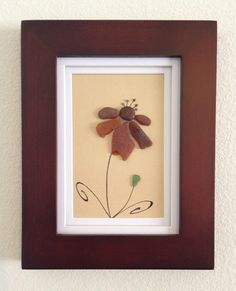 Genuine Brown and green sea glass collected from a beach from the central coast of California arranged in a collage to make flower with a