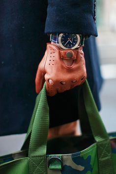 Bag, gloves & watch blends so perfectly with the solid navy coat! Wonder what else he's wearing?