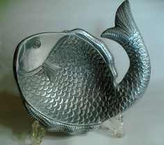 B10429 £28 inc UK post/offers welcome. A vintage or retro metal dish or desk tidy (believed to be aluminium) in the form of a fish standing on four integral feet.  There are a few very minor surface scratches and dinks which might be expected as aluminum is a relatively soft metal but the dish is otherwise structurally sound.  The dish measures approximately 7.875in across. For further info/photos, please see http://carterscollectablesuk.co.uk/Aluminium-Fish-Dish